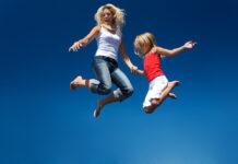 Mor og barn hopper på trampolin